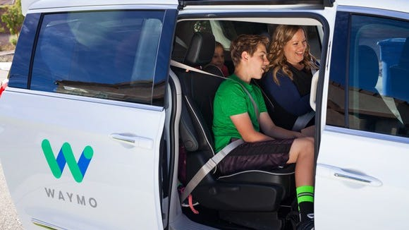 A mother and her son preparing for a ride in a Waymo self-driving minivan.