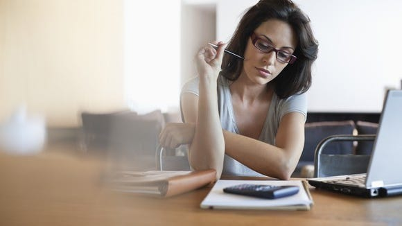 Woman looking at financial paperwork with a calculator