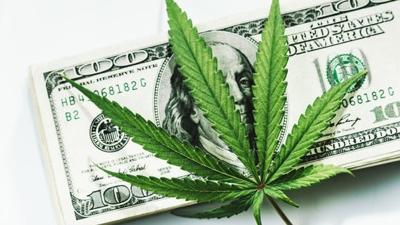 Marijuana leaf on top of stack of $100 bills