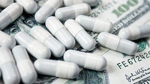 Prescription drug capsules lying on a messy pile of hundred dollar bills.