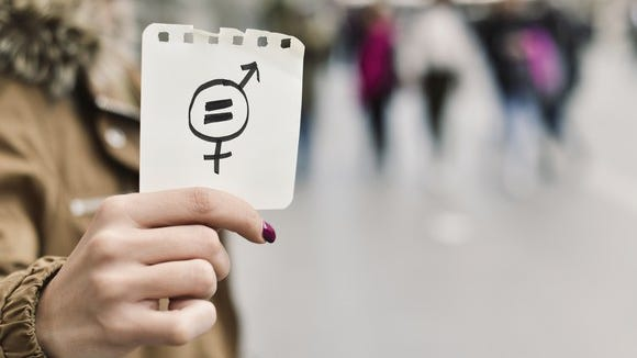 A woman holds a symbol for gender inequality.