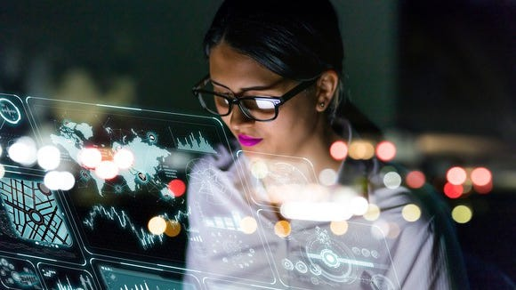Female engineer looking at data visualizations on multiple screens, reflected in glass.
