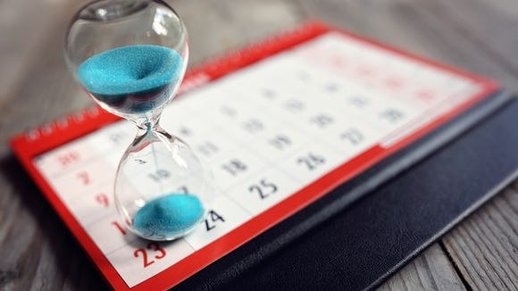 Image of an hourglass sitting on top of a calendar.