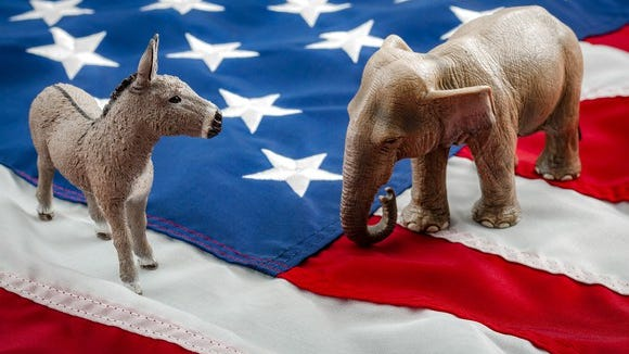 Miniature figures of a donkey and an elephant on an American flag.