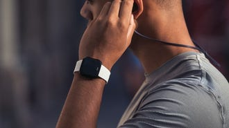 Man in workout gear wearing a Fitbit Versa Smartwatch