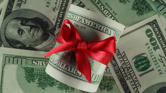 Roll Of Money Gift Wrapped In a Red Bow On Top Of More Cash