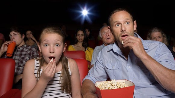 A father and daughter eating popcorn at a movie theater.
