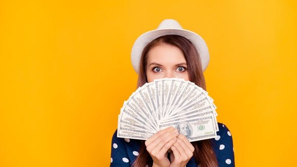 Woman holding money in front of yellow background.