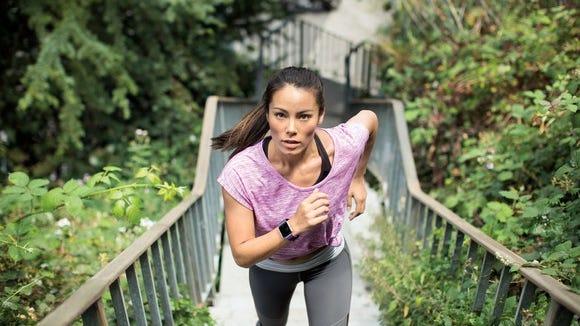 A runner donning a Fitbit blaze runs up a flight of stairs.