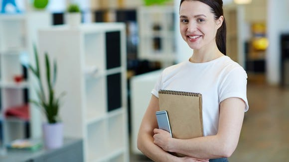Young female in an office holding a note pad and a smartphone.