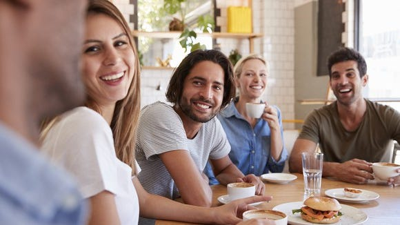 Group of millennial adults, sitting around a table.