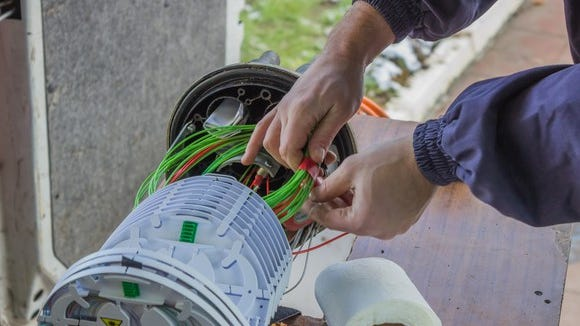 A technician is installing fiber-optic network connections to a wireless base station.