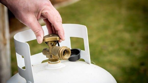 A hand turning a knob on a propane tank.