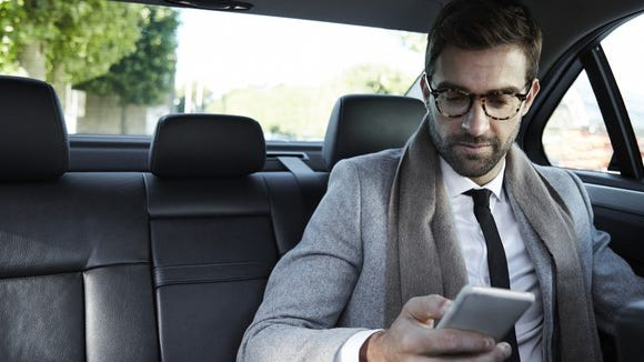 A businessman uses a smartphone in a taxi.