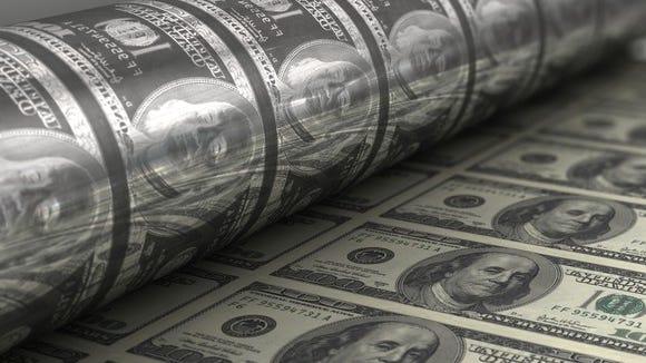 A press at the U.S. mint printing hundred dollar bills.