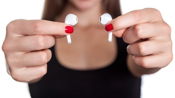 Close-up shot of a woman holding up two wireless earbuds.