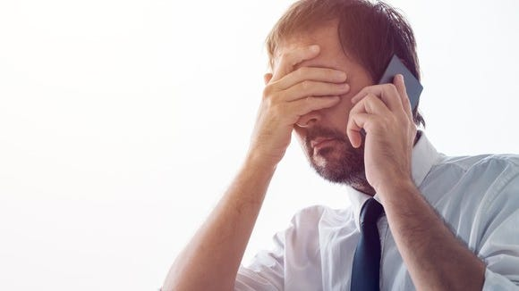 Person on phone with hand over eyes.