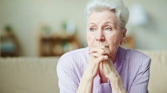 Older woman looking worried with her hands crossed