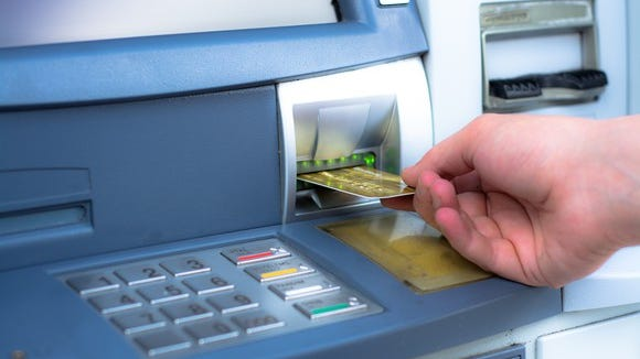 A person is pulling a debit card out of an ATM.