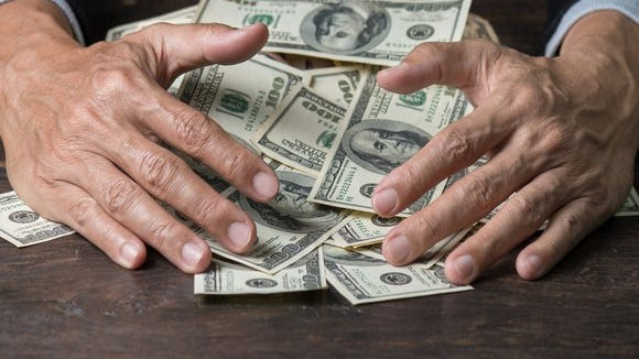 A man's hands taking a pile of cash off of a table.
