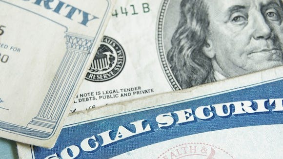 Two Social Security cards partially covering a hundred dollar bill.