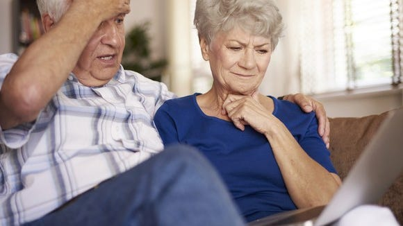 Older man and woman frown at a computer screen.