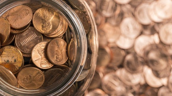 A jar of pennies surrounded by more pennies.