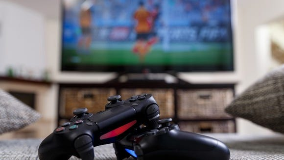 Pair of video game console controllers laying on the floor with a TV displaying a game in the background.