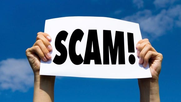two hands holding up a sign that says scam!
