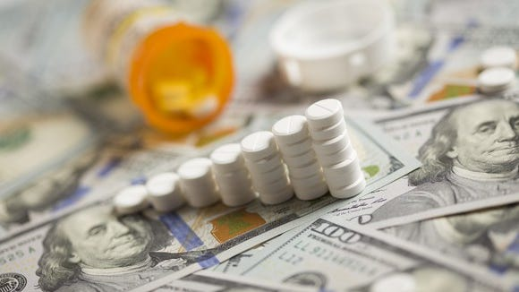 Prescription drugs arranged in the shape of an upward sloping chart, and situated on top of a pile of hundred-dollar bills. In the background is a tipped-over open prescription bottle.
