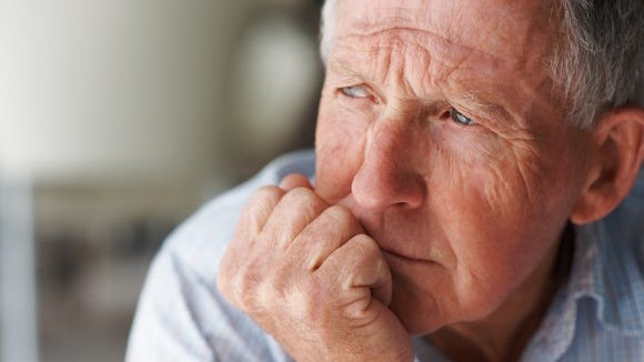 A visibly worried senior man looking into the distance with his head resting on his hand.