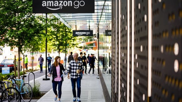 People walk along the sidewalk outside an Amazon Go location.