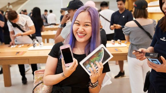 Woman holding up a new iPhone XS Max