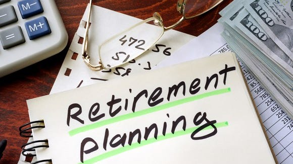 """Notebook that says """"retirement planning"""" on the cover, next to money, glasses, and a calculator."""
