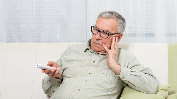 Older man holding TV remote with bored expression