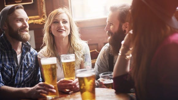 Four friends drinking beer at a bar.