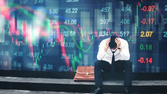 A businessman sits outside looking distressed while stock market numbers are displayed in the back.