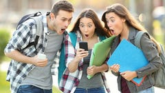 Three young people watch a video on a smartphone.