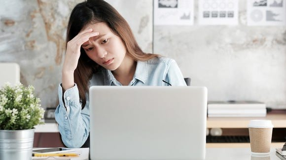 Woman sitting at a laptop holding her head as if stressed.