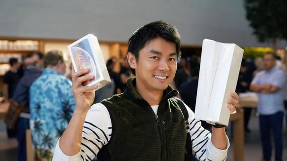 A man holding Apple products in an Apple store
