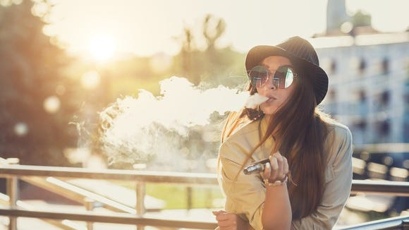 Female teen using vaping device