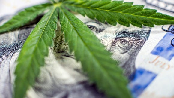 A cannabis leaf lying atop a hundred dollar bill and blocking Ben Franklin's face, save for his eyes.