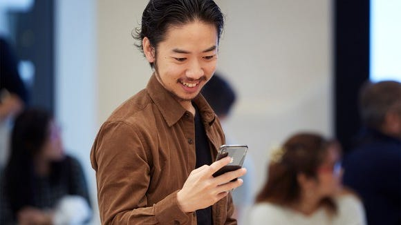A man holding and looking at an iPhone XS in space gray.