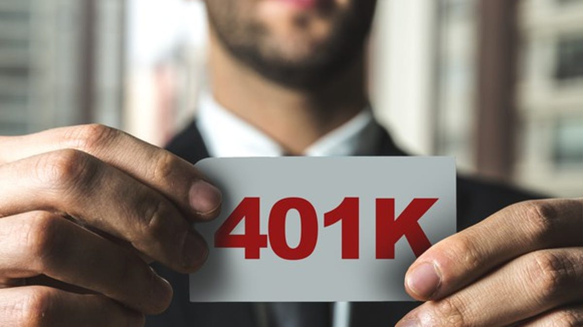 "Man holding a small sign spelling out ""401K"" in red letters."