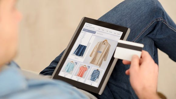 A man entering his credit card info into a tablet to make a clothing purchase.