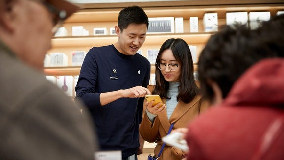 Retail employee showing a customer how to use an iPhone XR