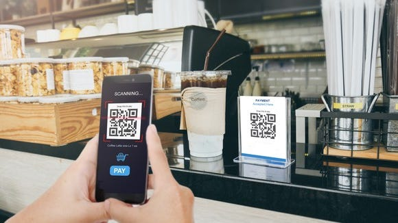 A customer paying for coffee with a QR code.