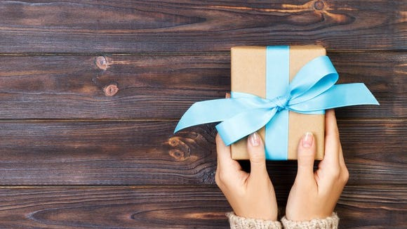 Two hands holding a small wrapped present with blue ribbon on a wood table.