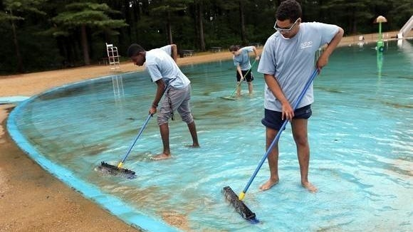 Crew members Zared Celentano, Vincent Cleare, and Ryan Knight swept the sand from the shallows of the Springs Brook Pond in the summer of 2017.