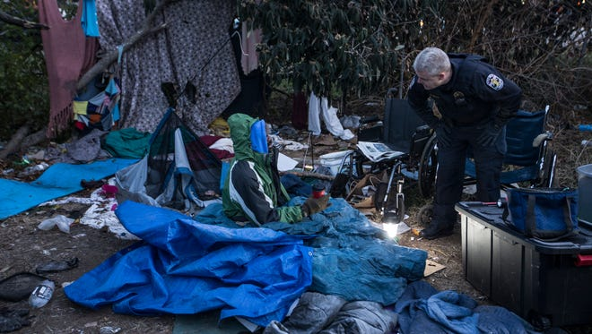 """Metro Louisville Police Lt. Todd Felty talks with Byron """"Roc"""" Peeler prior to removing him from a homeless camp between Jefferson Street and I-65. Dec. 8, 2017."""